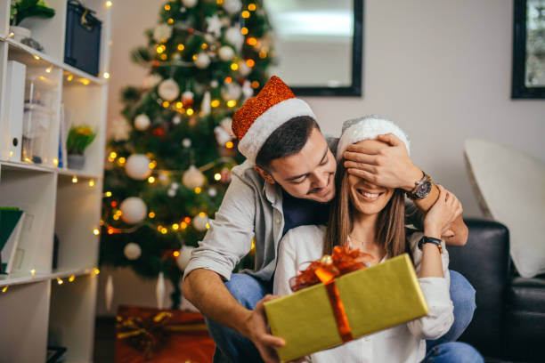 young couple celebrating christmas - milan2099 stock photos and pictures