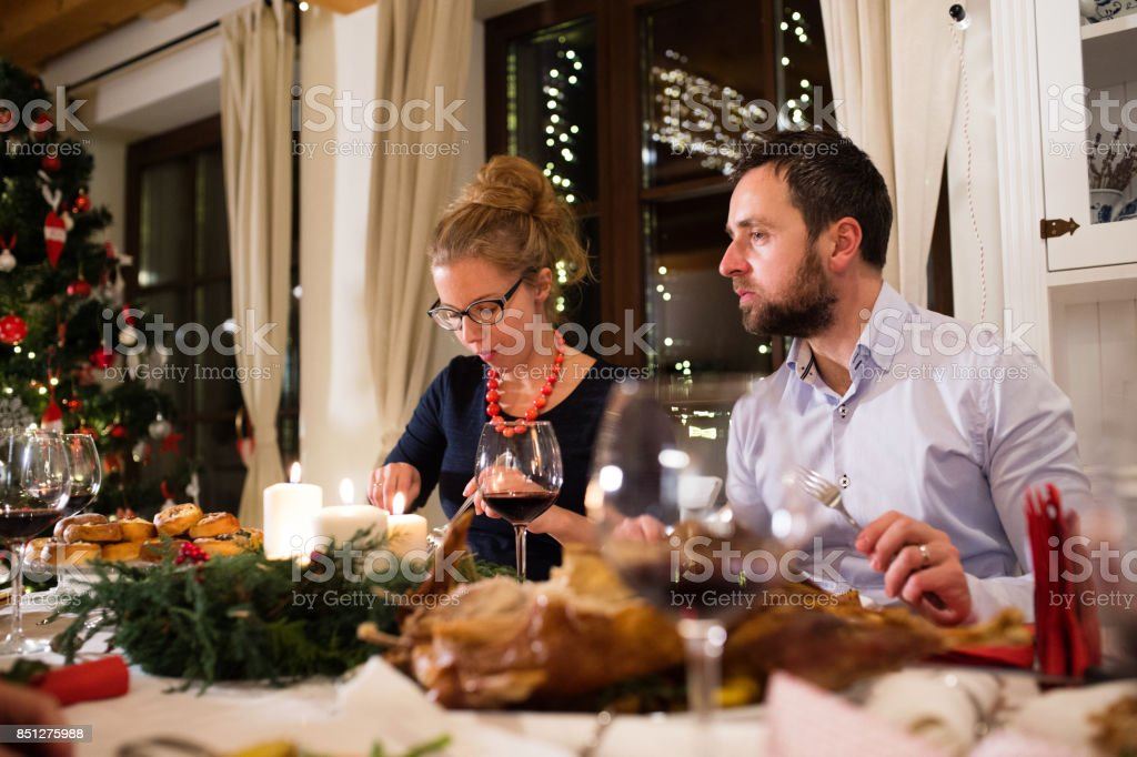 Young couple celebrating Christmas together at home. stock photo