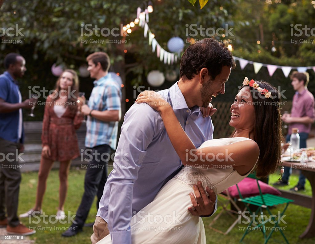 Young Couple Celebrating Wedding With Party In Backyard stock photo