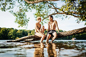 Young Couple Chatting Together While Sitting On Log At Lake