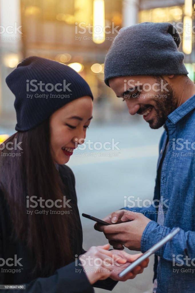 Junges Paar im Chat, mit Smartphone auf Stadtstraße – Foto