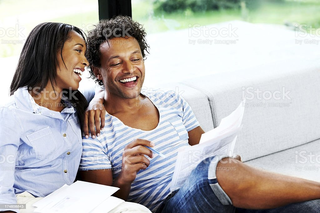 Young couple checking financial bill at home smiling stock photo
