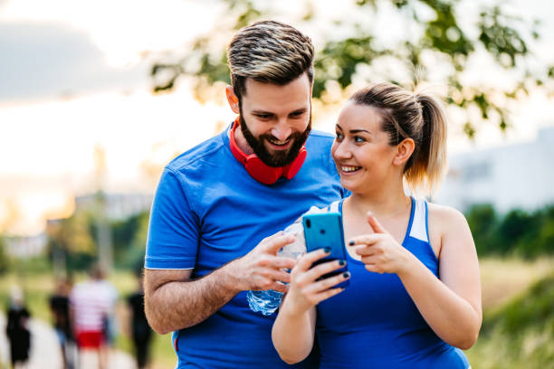Young couple checking fitness activity on phone stock photo