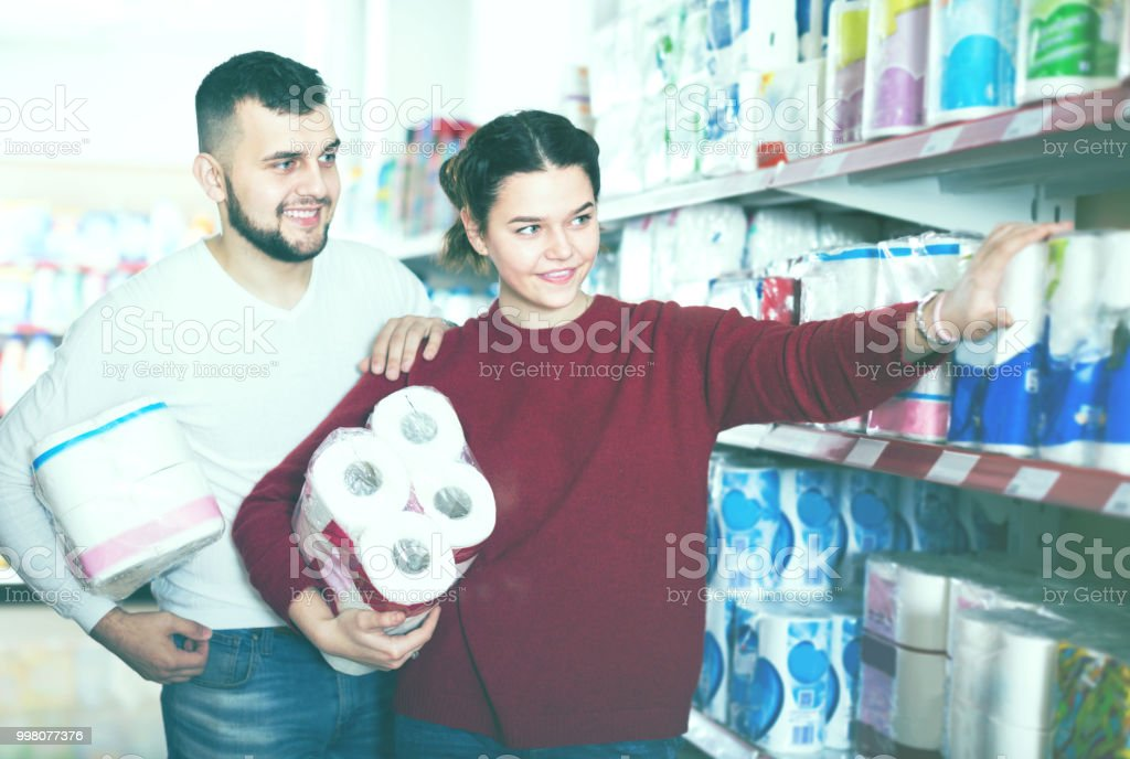 Young couple choose toilet paper in the shop stock photo