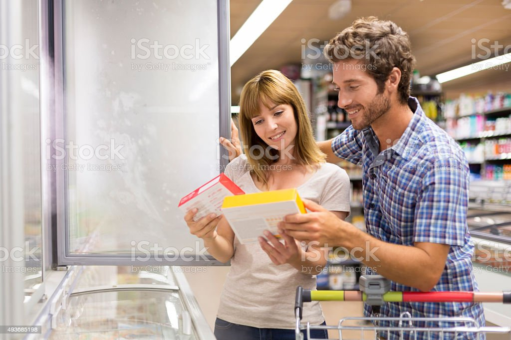 Young couple chooses frozen products in supermarket stock photo