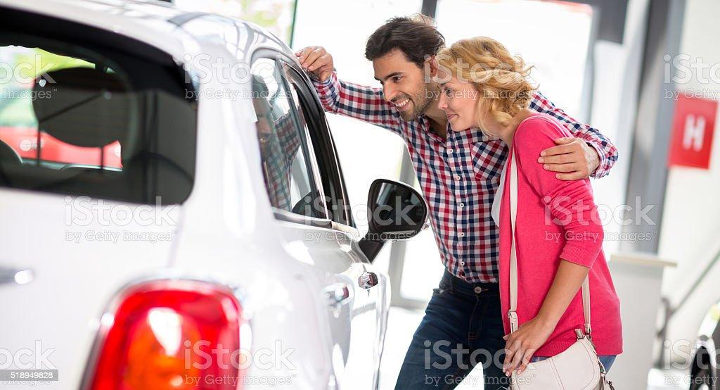 Jeune couple choisit d'acheter une voiture - Photo