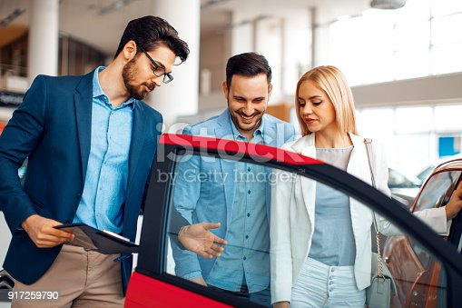 istock Young couple choosing new car for buying in dealership shop 917259790
