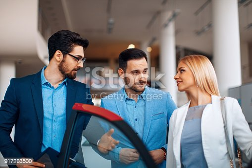 istock Young couple choosing new car for buying in dealership shop 917263500