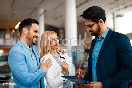 istock Young couple choosing new car for buying in dealership shop 917269384
