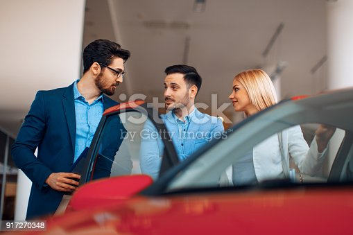 istock Young couple choosing new car for buying in dealership shop 917270348