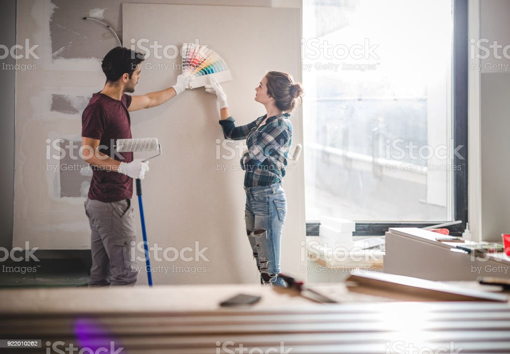 Young couple choosing the right color for their wall while renovating apartment. royalty-free stock photo