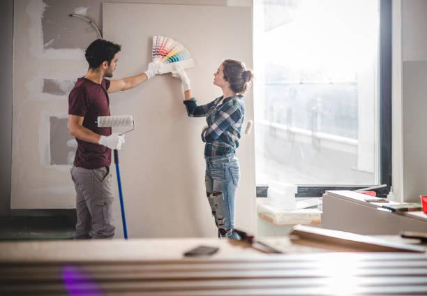 молодая пара выбирает правильный цвет для своей стены при ремонте квартиры. - краска стоковые фото и изображения