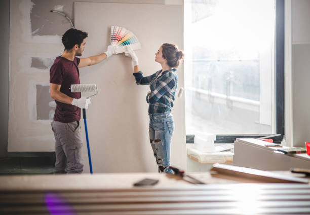 Young couple choosing the right color for their wall while renovating apartment. stock photo