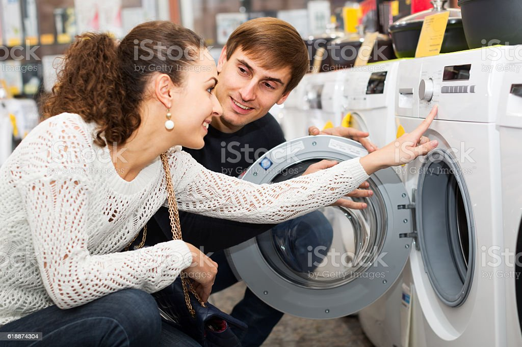 Young couple choosing washing machine in hypermarket and smiling stock photo