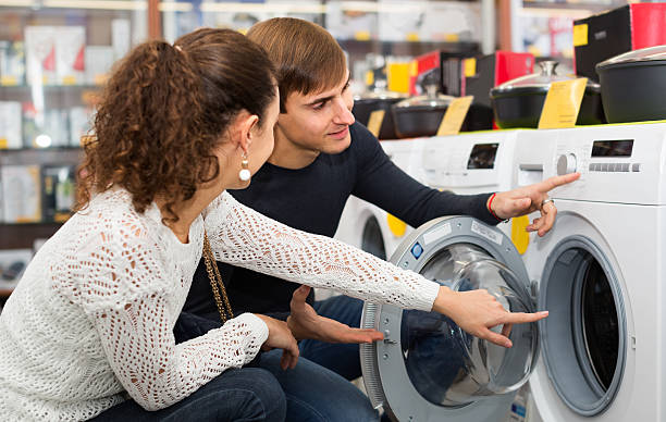 young couple choosing washing machine - happy person buy appliances stock photos and pictures