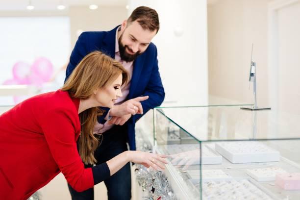 junges paar trauringe bei juwelier zu wählen. - diamanten kaufen stock-fotos und bilder