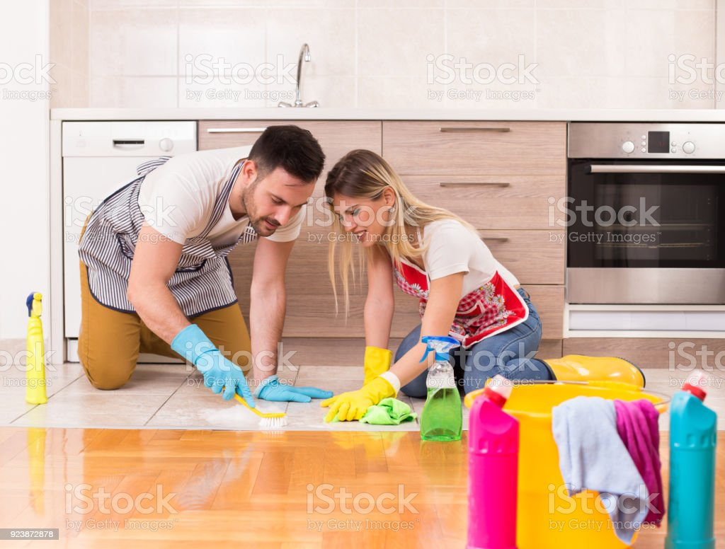 Young couple cleaning kitchen floor with brush and wipe. Teamwork in...