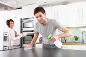 Young Couple Cleaning Modern Kitchen With Sprary And Cloth