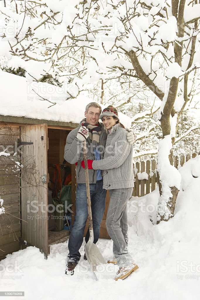 Young Couple Clearing Snow From Path To Wooden Store royalty-free stock photo