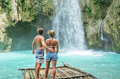 Young couple contemplating a beautiful waterfall on the Cebu Island in the Philippines. People travel nature loving concept. Honeymooners enjoying outdoors and tranquillity in a peaceful environment