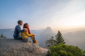 Young couple contemplating sunrise from top of Yosemite valley, USA