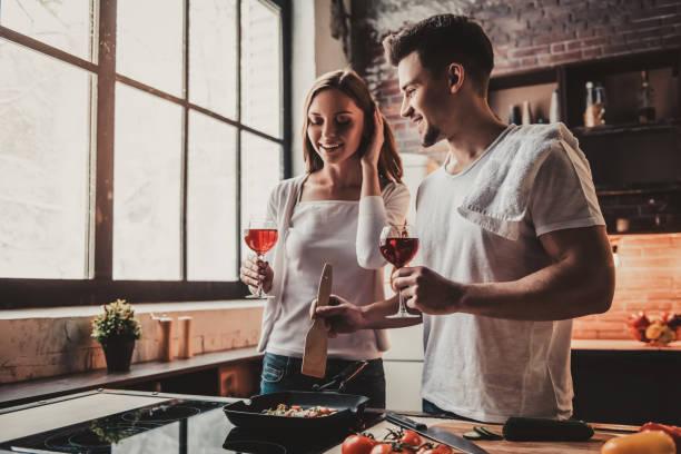 Junges paar kocht Essen und trinken Rotwein. – Foto