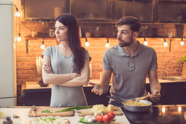 young couple cooking in kitchen - fighting stock photos and pictures