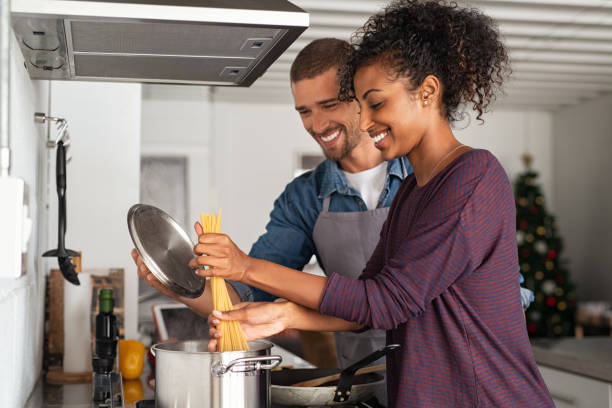 Young couple cooking italian pasta stock photo
