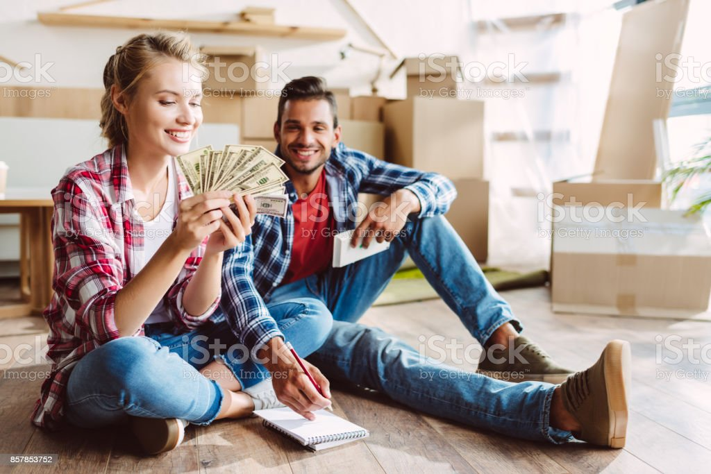 young couple counting money stock photo