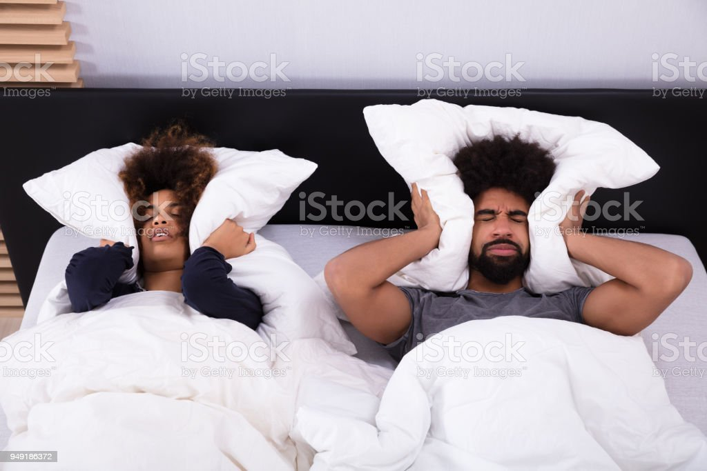 Young Couple Covering Their Ears With Pillow stock photo