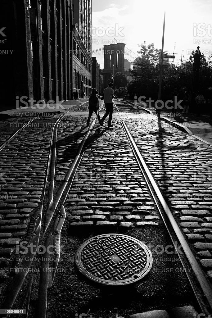 Young couple cross cobblestone street in DUMBO Brooklyn sunset stock photo