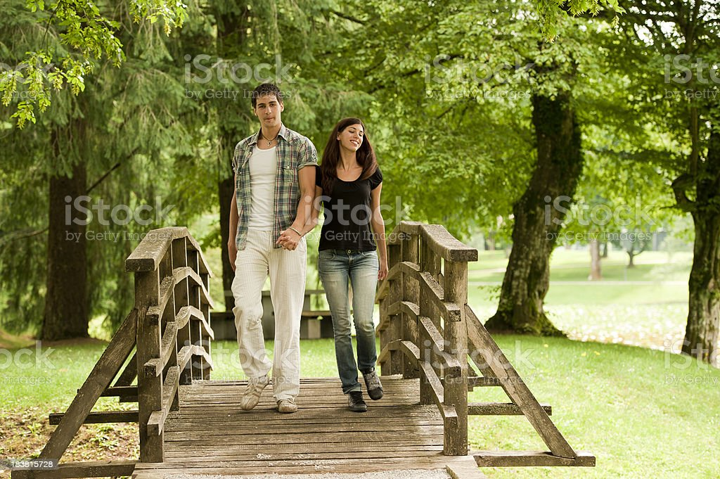 Young couple crossing the bridge royalty-free stock photo
