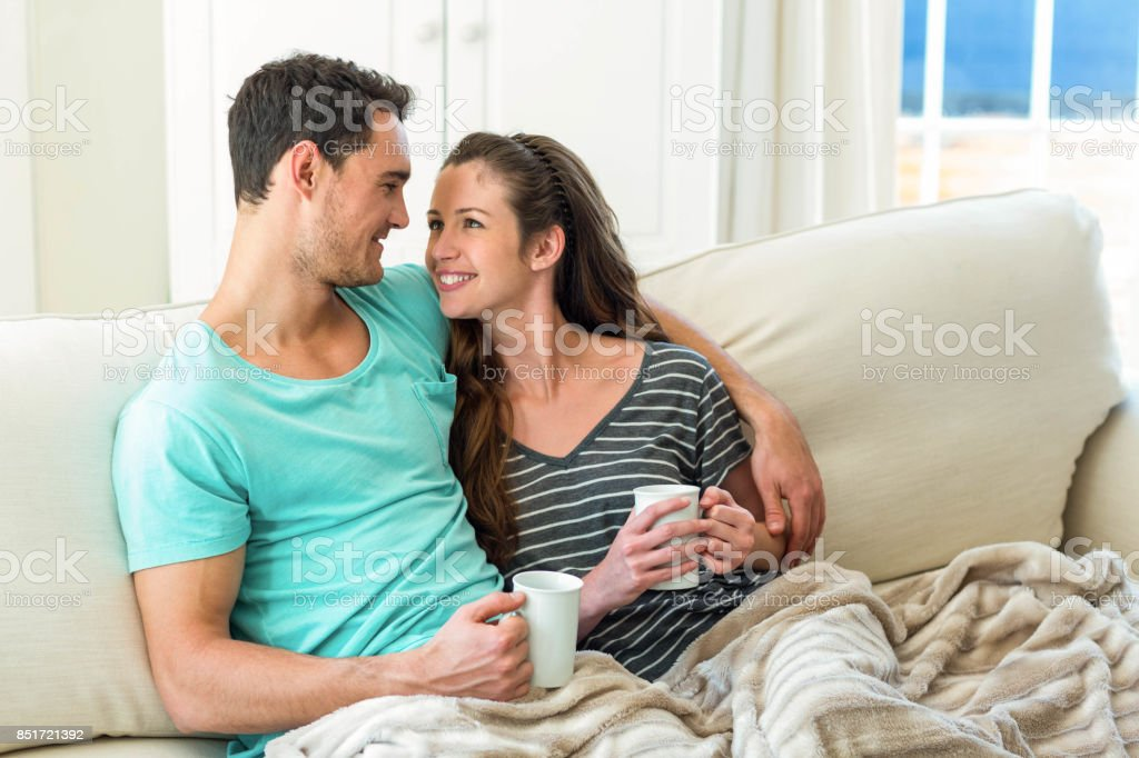Young Couple Cuddling On Sofa While Having Coffee Royalty Free Stock Photo