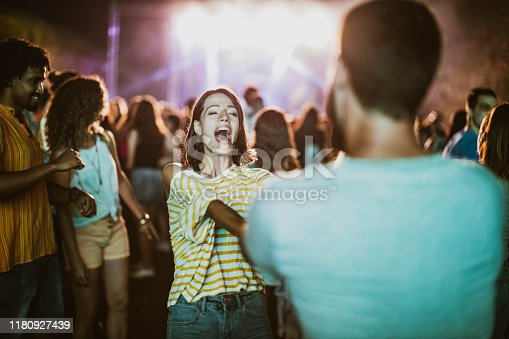 Carefree couple having fun while dancing on music festival by night.