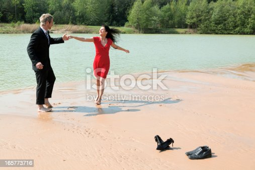 Young couple dancing barefooted on sand lakeside.