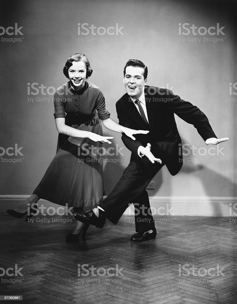 Young couple dancing in empty room, (B&W) stock photo