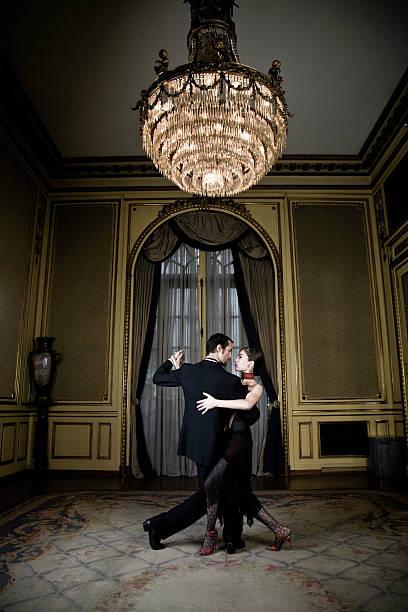 junges paar tanzen tango in eleganten zimmer - alten kronleuchter stock-fotos und bilder