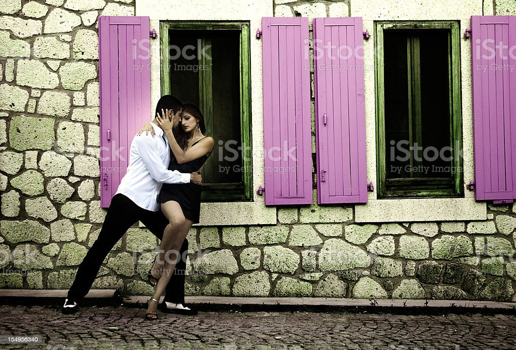 A young couple dancing tango next to a wall made of rocks stock photo