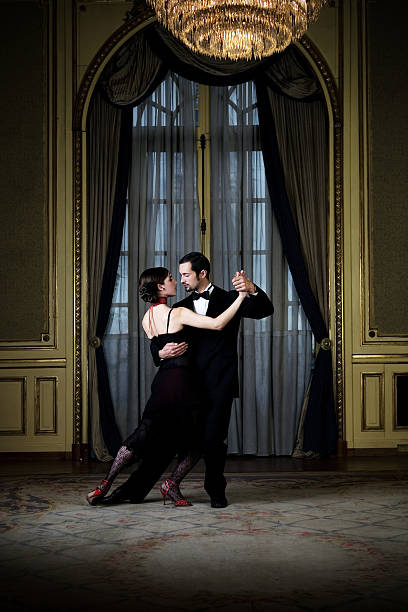 Young couple dancing the tango in an elegant room stock photo