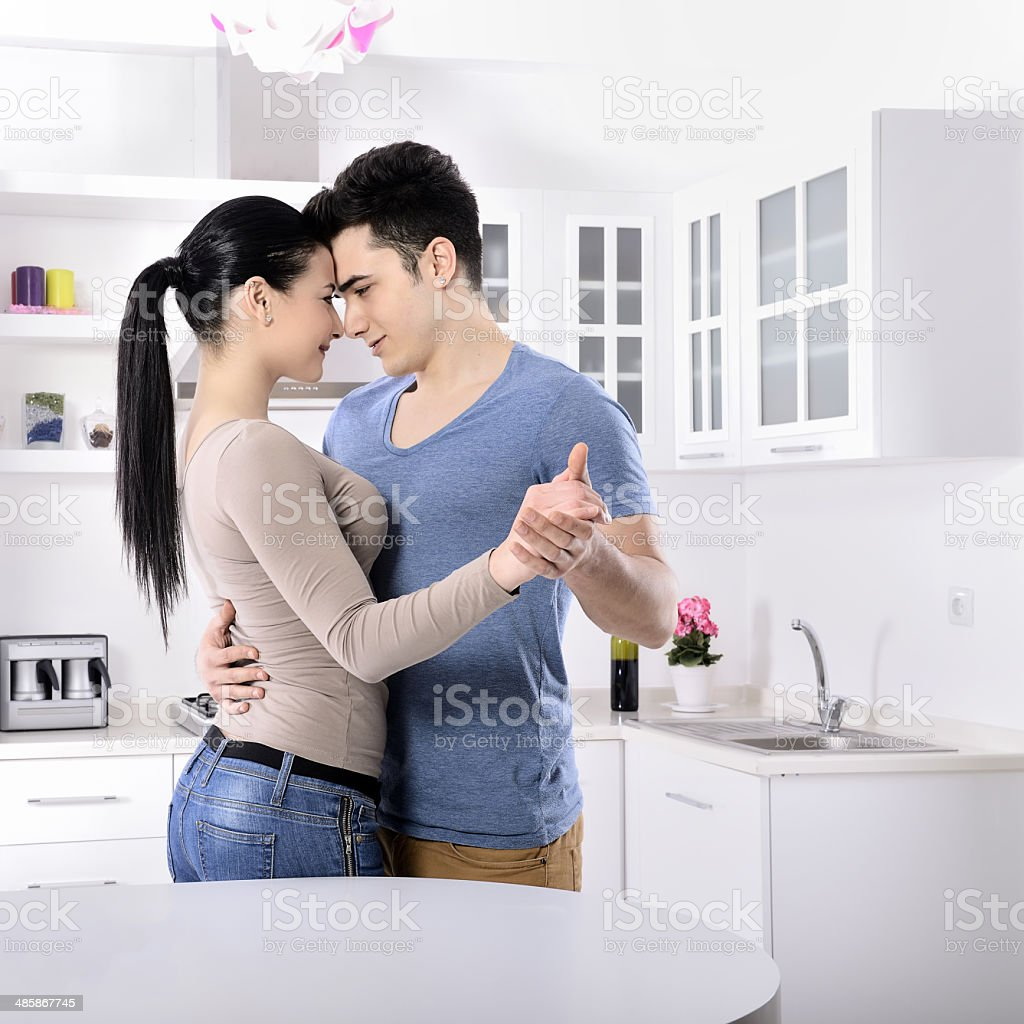 Young couple dancing together in the kitchen stock photo
