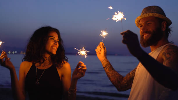 Young couple dancing with sparklers on the beach stock photo