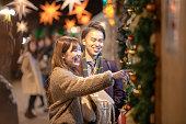 クリスマス マーケットでデートする若いカップル