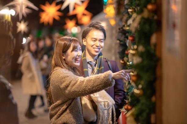 junges paar aus dem weihnachtsmarkt - weihnachten japan stock-fotos und bilder
