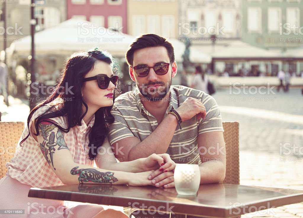Young couple dating in the outdoor restaurant Happy young couple wearing sunglasses dating in outdoor restaurant in the city, sitting at the table and holding hands. Woman has tatoo on her arm. Summer time.  2015 Stock Photo