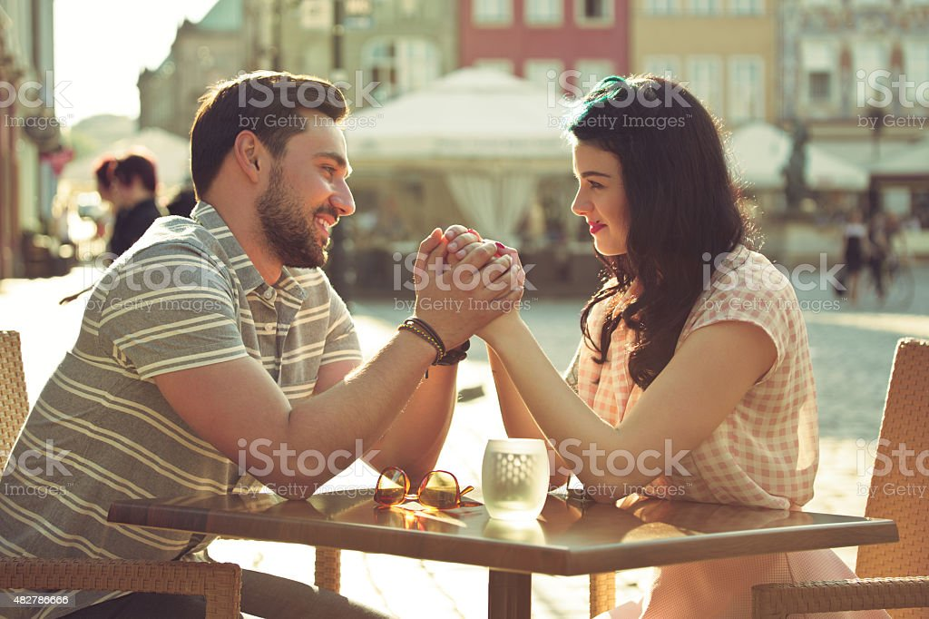 Young couple dating in the outdoor restaurant Happy young couple dating in outdoor restaurant in the city at sunset, sitting at the table and holding hands, looking at each other. Summer time.  2015 Stock Photo