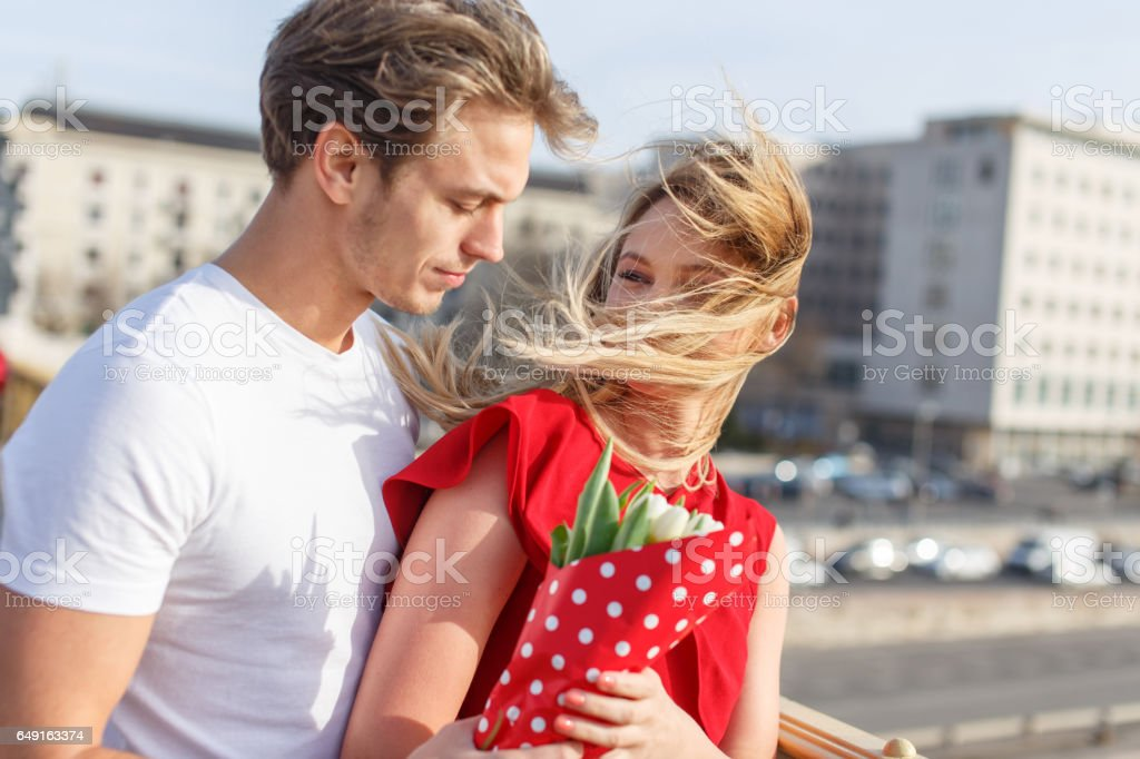 Young couple dating on bridge at windy spring day stock photo