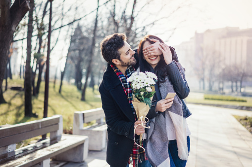 Cheerful young man surprising his girlfriend with spring flowers bouquet and hiding her eyes with hand