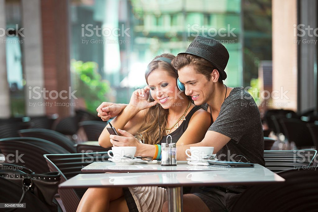 Young couple dating Cheerful young couple sitting in cafe, listen to the music on mp3 player.  20-24 Years Stock Photo