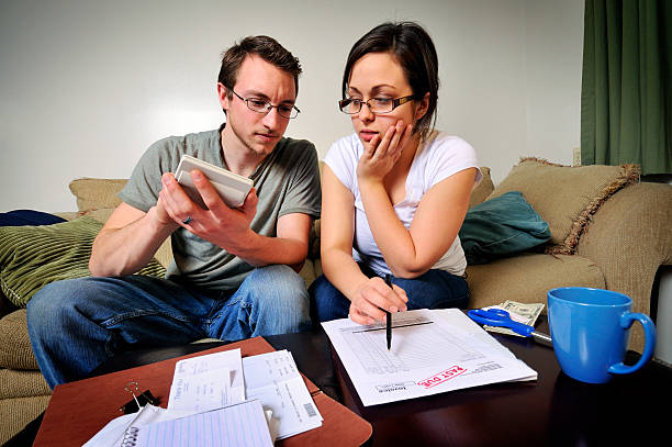young couple dealing with their finances - mike cherim stock pictures, royalty-free photos & images