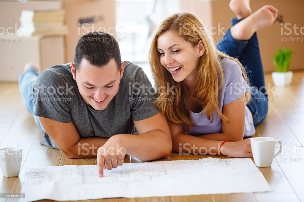 Young couple deciding where to put all their furniture stock photo